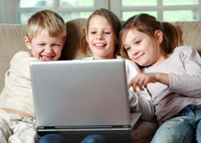 Three Kids Play Games on a Laptop