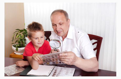 Boy and Grandfather Look at Coin Collection