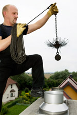 Chimney sweep on Roof with Chain Brush