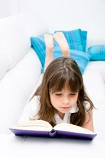 Small girl Reading a Book on Sofa