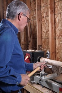 Man Using Lathe to turn Wood Block