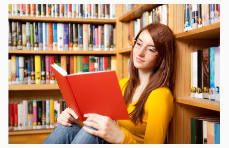 Teen Girl Reads Book in Library