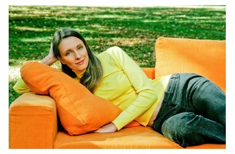 Reclining Woman on Orange Sofa Outdoors