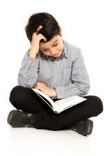 Young Boy Sits Cross Legged with Book